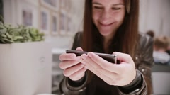 Pretty young woman with dark hair in a leather jacket using her smartphone Stock Footage