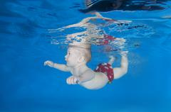 5 months infant boy learning to swim underwater in waterbaby class in the pool Stock Photos