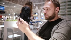 Handsome man with a beard using his smartphone in a cafe. Modern technology Stock Footage