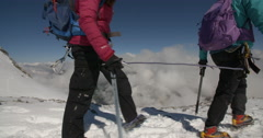 Two Mountaineers Decending Icy Glacier above the Clouds. Stock Footage