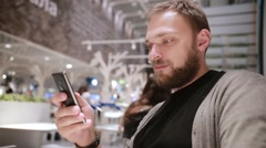 Young handsome man with a beard sits in a cafe, uses his smartphone, smiles and Stock Footage