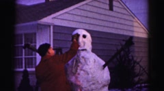 1962: teenage boy building a snowman in winter HAGERSTOWN, MARYLAND Stock Footage