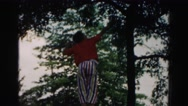 1962: boy in striped pants and an orange shirt playing in a tree HAGERSTOWN Stock Footage