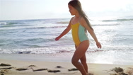 Slow motion of a cute little girl in swimsuit playing at the sea beach Stock Footage