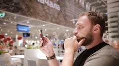 Sideview of a man holding a smartphone in his hand, sitting in a public place Stock Footage