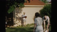 1962: man picks child up by wrists and ankles, then swings him around as people Stock Footage