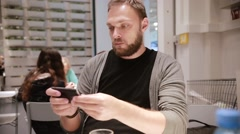 Modern technology in a public place. Handsome young man with a beard using his Stock Footage