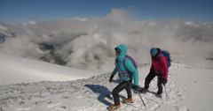 Mountaineers Crossing High Altitude Glacier Above the Clouds. Stock Footage