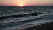 Sunset. Sea waves rolling to the sandy beach in the rays of the setting sun. HD Stock Footage