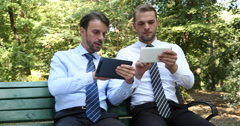 Confident Businessmen Talking Using Tablet Teamwork Collaboration in Park Bench Stock Footage