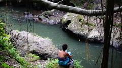 Female on bank of jungle river. Stock Footage