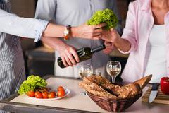 People cooking together healthy food in the kitchen at home Stock Photos