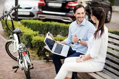 Smiling man with a laptop talking to his colleague Stock Photos