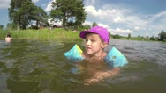 Child, little girl swimming in pond water, beach Stock Footage