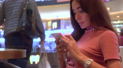 Pretty brunette girl in pink using her telephone in a cafe. Mobile phone Stock Footage