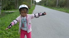 Little girl learns to roller skate on the village road Stock Footage