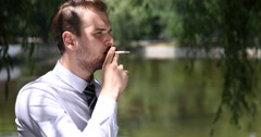 Business Male Smoking Cigarette Looking Out Sitting on a Comfortable Park Bench Stock Footage