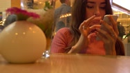 Beautiful young woman in pink using her telephone in a cafe. Mobile phone Stock Footage