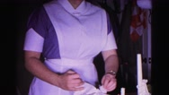1962: woman in a nurse outfit carefully unwraps and then opens a box  Stock Footage