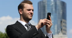 Serious Businessman Searching Mobile Phone in Front of Modern Office Building Stock Footage