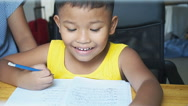Little asian boy doing homework by use pencil writing on notebook. Stock Footage