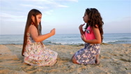 Two little girls playing on the sea beach, slow motion Stock Footage