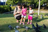 Asian Chinese Mother and Daughter Feeding Pigeons Stock Photos
