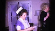 1962: woman in what appears to be a nurse's uniform opens an envelope Stock Footage