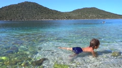 Child dabbling in the crystal clear sea water Stock Footage