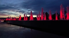 Modern red lit park fountains against late sunset sky. Architectural LED Stock Footage