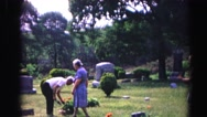 1962: a family gathers on a peaceful cemetery to bring flowers  Stock Footage