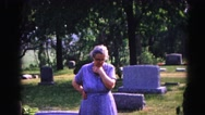1962: a woman standing alone in a cemetery looking down at a grave HAGERSTOWN Stock Footage
