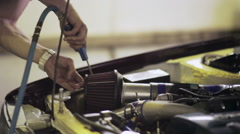 Worker blows away the dust off the car engine Stock Footage