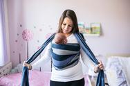 Beautiful young mother wrapping her son into sling Stock Photos