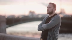 Handsome man standing on a quay, folding his arms on a chest. Man with a beard Stock Footage