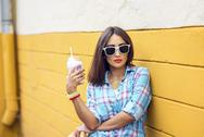 Woman in the city on the background of a yellow wall, holding  milkshake, fresh Stock Photos