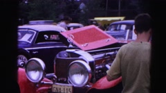 1962: a group of cars on a car show with spectators admiring the antique cars Stock Footage