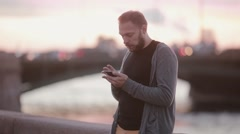 Handsome man using his gadget. Man using a smartphone standing on a quay. Cars Stock Footage