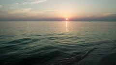 Sunrise. Sea waves coming up on the sandy shore in rays of the rising sun. HD Stock Footage