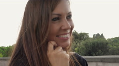 Smiling woman sitting on a stone bench in the city: handled shot Stock Footage