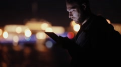 Handsome man, smiles, nods, uses his tablet at night, then goes away. Blurred Stock Footage