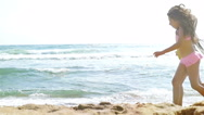 Two little girls running on the sea beach, slow motion Stock Footage