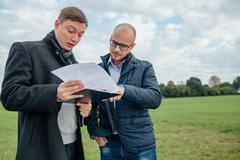 Two young investors are looking at the investment papers. One of them is shoc Kuvituskuvat
