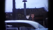 1962: driving past a town block passing cars, pedestrian and buildings. Stock Footage