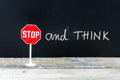 STOP and THINK message written on chalkboard Stock Photos