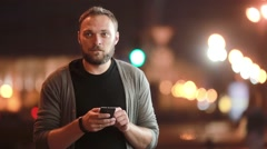 Handsome man texts, uses his smartphone and goes away. Blurred city lights in Stock Footage