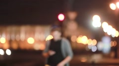 Handsome man walks, smiles, uses his smartphone and goes away. Blurred city Stock Footage