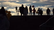 Silhouettes of people walking upstairs and downstairs against evening sky. Slow Stock Footage