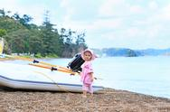 Little girl in pink dress standing by motor boat on pebble beach  .Russell Lo Stock Photos
