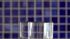 Clean fresh water drops falling in a full glass that is overflowing. Stock Footage